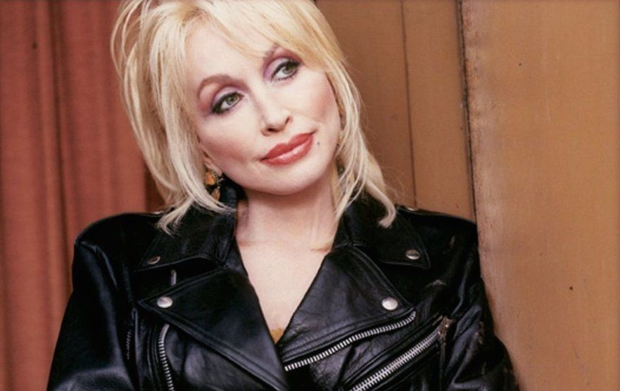 Dolly Parton wearing black leather jacket,  looking to the side