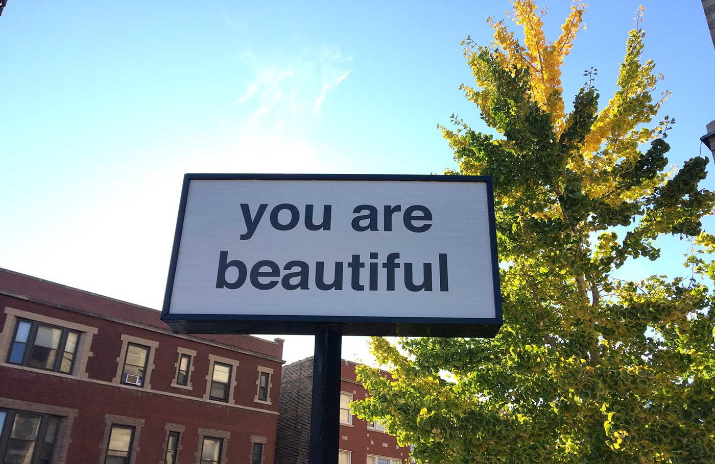 "Sign that has text ""You Are Beautiful"" against blue sky"