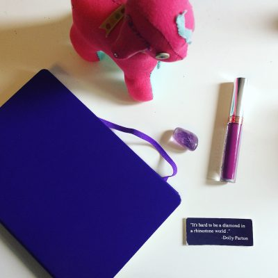 Overhead shot of journal, plush, lipstick and amethyst on white background